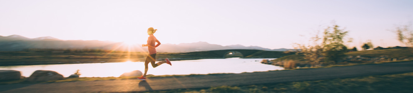 Woman jogging around a lake with the sun setting