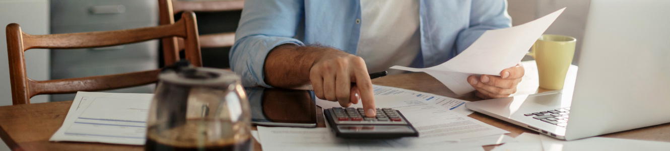 Man sitting at a table using a calculator